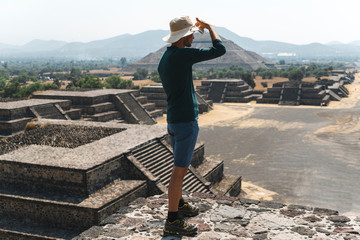 Tourist with hat and looking to Teotihucan Ruins, Mexico