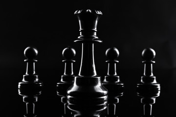 Chess figures on dark black background close up