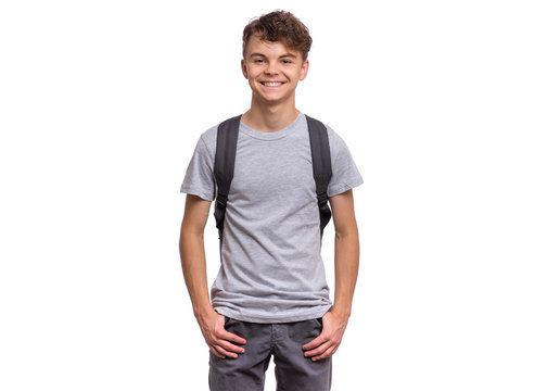 Student teen boy with backpack looking at camera. Portrait of cute smiling schoolboy with hands in pockets, isolated on white background. Happy child Back to school.
