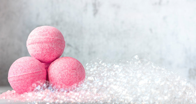 Pink bath balls on a background of soapy foam. Banner or background, copy space.
