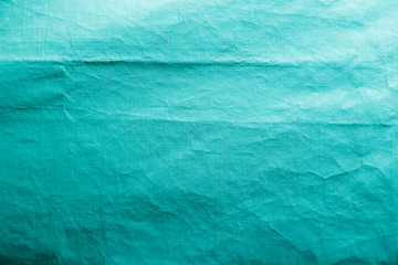 Dirty crumpled turquoise synthetic fabric texture with a well-traced light and shadow pattern