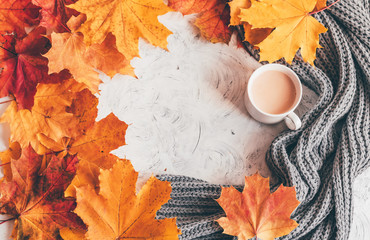 Wall Mural - Autumn home cozy composition a cup of coffee with maple leaves.Top view