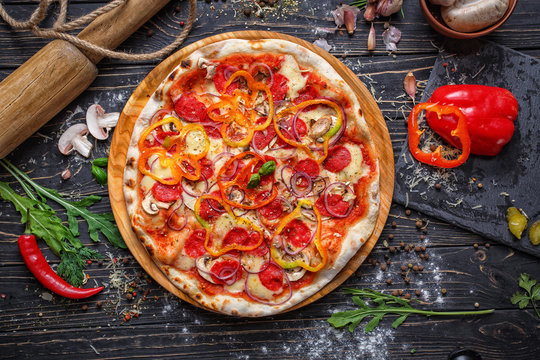 Pizza with fragrant sausages, onions and peppers
