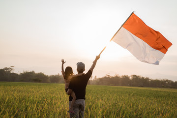 father carrying little girl pride flapping Indonesian flag with happiness in the rice field