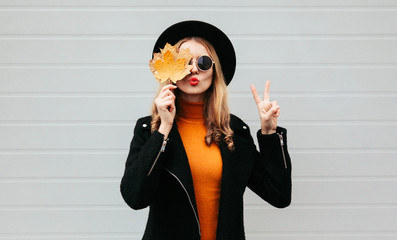 Stylish woman closes her eyes with yellow maple leaves blowing red lips sending sweet air kiss, female model in black coat, round hat on city gray wall background Wall mural