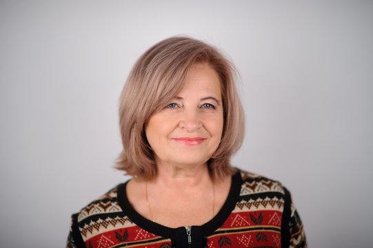 portrait of senior woman over grey background. Studio picture