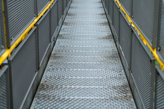 Pedestrian bridge of metal in an industrial facility with yellow railings