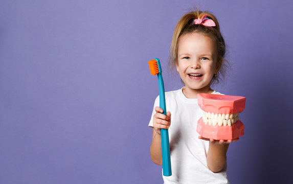 Laughing kid girl shows us big dental implant model and giant toothbrush on purple with free text copy space