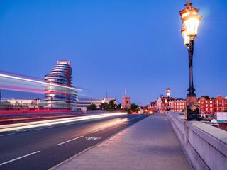 Red double decker bus trails on Putney bridge agains blue sky in London