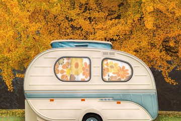 Vintage seventies white caravan with flower curtains in front of