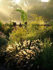 Vertical image of a country garden in fall (autumn) with flowers, ornamental grasses, an arbor (arch), and fence lit by sunbeams from sunrise