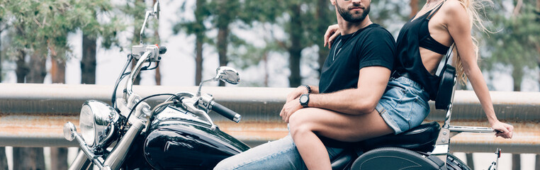 cropped view of young couple of bikers on black motorcycle on road, panoramic shot Fototapete