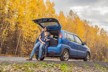 Dad and son are resting on the side of the road on a road trip. Road trip with children concept