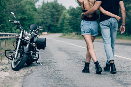 cropped view of young couple of bikers walking along road and embracing near black motorcycle