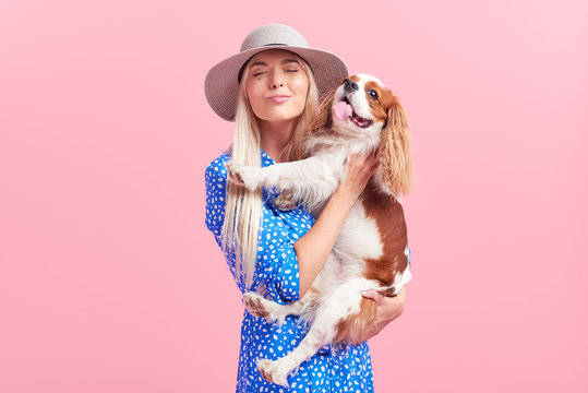 Portrait of smiling young blond woman in summer hat embracing king Charles spaniel dog. owner and pet relations concept. Veterinary health. Isolated front view on pink background.