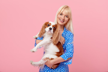 Portrait of smiling young blond woman in summer hat embracing king Charles spaniel dog. owner and pet relations concept. Veterinary health. Isolated front view on pink background. Wall mural