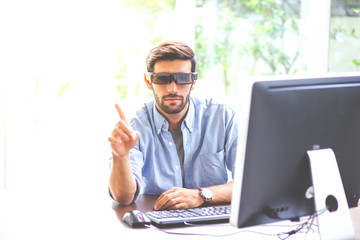Portrait of young business man try trying Virtual Reality or augmented reality in modern office