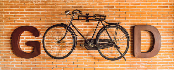 Inscription GOOD written with letters and a bicycle on the background of a brick wall. Eco-friendly transport concept. Moving from car to bike