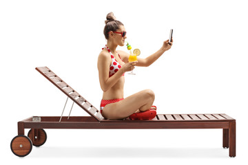 Young female in bikini sitting on a sunbed with a cocktail and taking a selfie photo