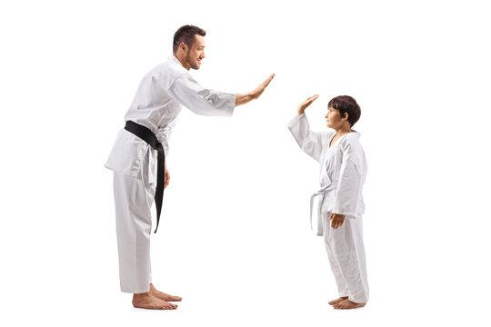 Boy and man in karate kimonos gesturing high-five