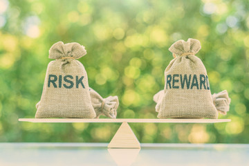 Risk reward ratio / risk management concept : Risk and reward bags on a basic balance scale in equal position, depicts investors use a risk reward ratio to compare the expected return of an investment