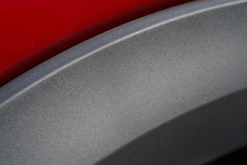 Close up detail of red metallic paint coating and carbon mat grey wrap car body