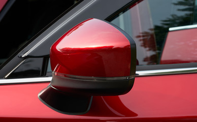 Close up of the side mirror of a red car