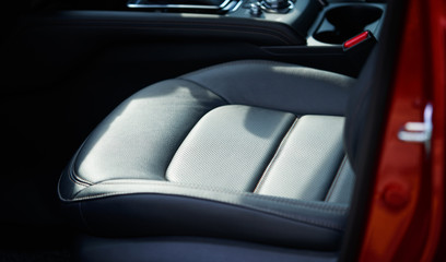 Closeup of a modern car interior with the black leather front seats