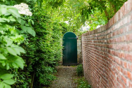 narrow access path to a wooden garden gate