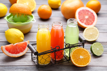 Citrus juice in glass bottles with fruits on wooden table