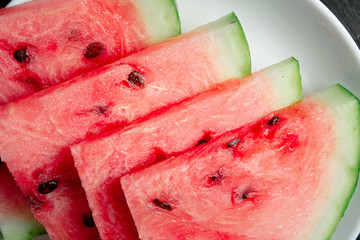 Slices of watermelon in dark background, top view. Delicious ripe watermelon served on a table