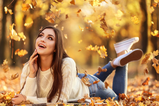 Beautiful woman lying on the ground in autumn park