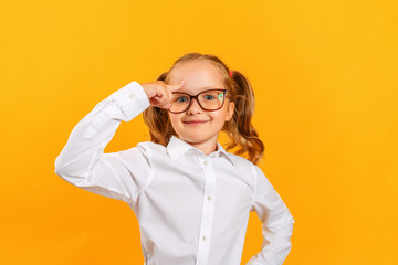 A little girl with glasses holds a finger to her head, an idea came up in a child. Education concept.