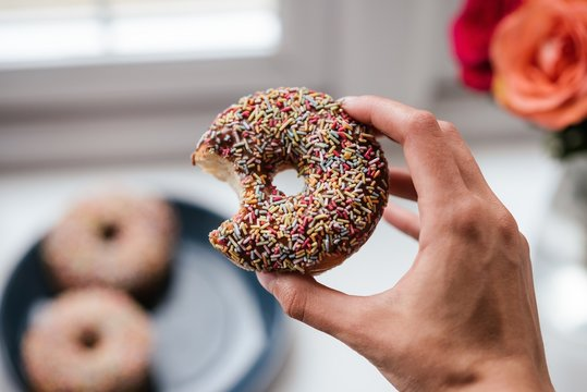 Closeup of a person holding a donut with a blurred background