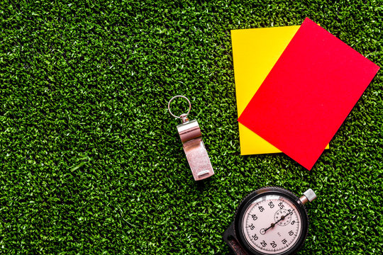 red and yellow cards on green background top view