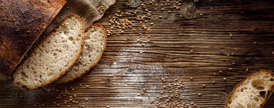 Bread,  traditional sourdough bread cut into slices on a rustic wooden background, close-up, top view, copy space. Concept of traditional leavened bread baking methods