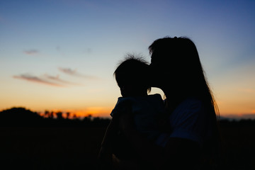 Silhuoete picture with copy space of mother and  her baby in the moment of love and  romantic among the twilight sunset evening time. Concept for love of parents and family.