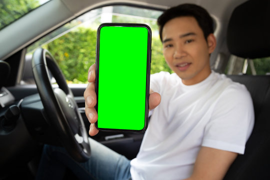Asian man driver sitting in the car and holding mobile phone with green screen background