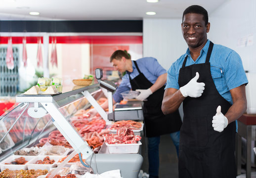 Happy African American seller of butcher store standing behind counter, giving thumbs up