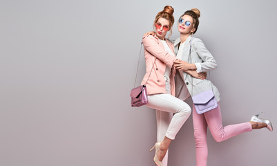 Wall Mural - Fashionable autumn woman sisters well dressed with stylish hairstyle, makeup. Two Shapely blonde redhead Girl Having Fun, Trendy coral pink outfit, fashion hair. Gorgeous female model,autumnal concept