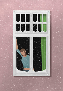 A woman standing by a window with snow falling outside