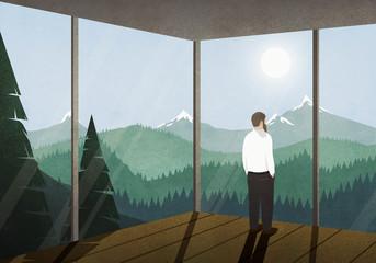 Man enjoying idyllic mountain view from house