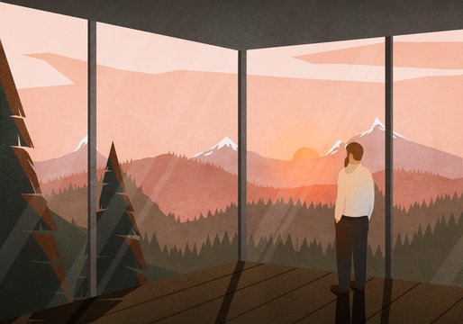 Man enjoying tranquil view of sunset behind mountains from glass house