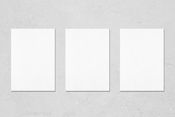 Three empty white vertical rectangle poster mockups with soft shadows on neutral light grey concrete wall background. Flat lay, top view Wall mural