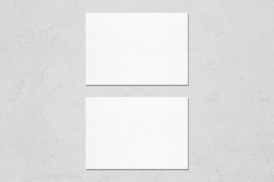Two empty white horizontal rectangle a5 sized card mockups with soft shadows on neutral light grey concrete wall background. Flat lay, top view