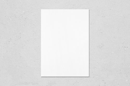 Empty white vertical rectangle poster mockup with soft shadow on neutral light grey concrete wall background. Flat lay, top view