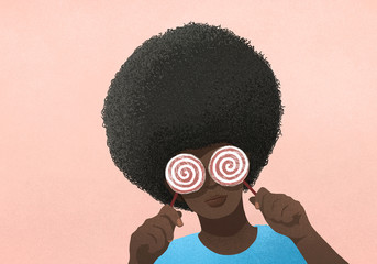Portrait woman with afro holding lollipops over eyes