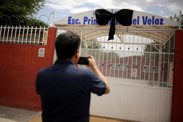 A man takes pictures of a black ribbon, placed in memory of teacher Elsa Mendoza, who died in the El Paso Walmart shooting, in Texas, U.S., outside the Rafael Veloz elementary school in Ciudad Juarez