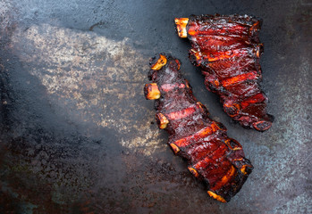 Barbecue chuck beef ribs with hot marinade and chili sauce as top on a old rustic board with copy space left