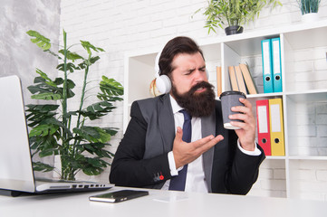 Successful businessman. Man office worker listening music headphones. Regular morning in office. Motivational music. Stress resistance concept. Manager relaxing with favorite music and cup of coffee